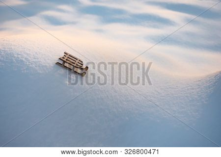 Toy On White Snow. Sleigh On Snowy Hills And Valleys. Toy Of Wooden Sleigh On Snow Background. Greet