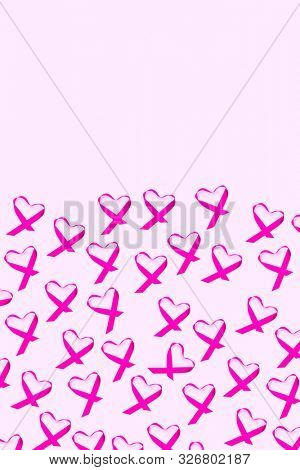 some pink awareness ribbons for the breast cancer awareness, placed as hearts, on a pale pink background with some blank space on top poster