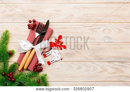 Top View Of Flatware Tied Up With Ribbon On Napkin On Wooden Background. Christmas Decorations And R