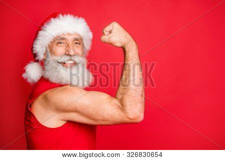 Close Up Photo Of Cheerful Santa Claus In Hat Cap With White Hairstyle Showing His Biceps Gymwearing