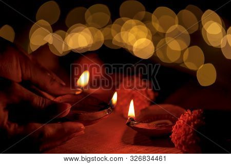 Indian Woman, Female Hand Holding And Lighting Up Diya Or Clay Oil Lamp During Indian Hindu Festival