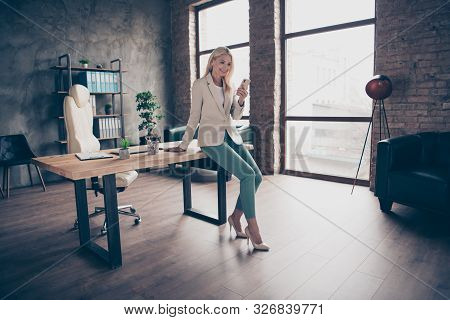 Full Size Photo Of Confident Focused Middle Aged Leader Business Woman Sit On Wooden Table In Office