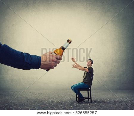 Alcohol Addicted Man, Hands Outstretched, Receiving A Huge Bottle Of Beer From An Unknown Person Han
