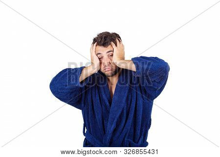 Portrait Of Tardy Young Man Wears Blue Bathrobe Holding Hands To Head, Unable To Wake Up In Time To