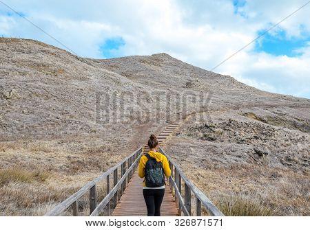 Young Girl In Yellow Sweater On Hiking Path In Ponta De Sao Lourenco In Madeira, Portugal. Peninsula