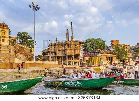 Varanasi, India - May 5, 2012: People Cross The Ganges By Ferry At Famous Ghat, In Holy Varanasi, Ut