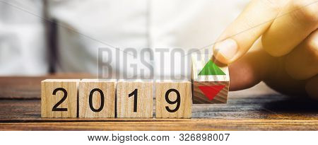Businessman Puts Wooden Blocks 2019 And Up Or Down Arrow. Summing Up The Year. Financial And Economi