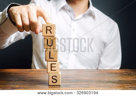 A man holds a tower of blocks with the word Rules from falling. Setting clear rule and restrictions. Leadership and discipline. Authoritarianism, tight control framework. Norms and laws in society poster