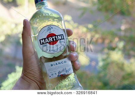 Kharkov, Ukraine - September 23, 2019: Bottle Of Vermouth Martini Rossi In Male Hand On A Green Tree