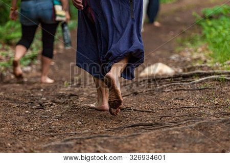 A Close Up View On The Bare Feet, Covered In Mud And Dirt, As They Walk On Sacred Soil During A Spir