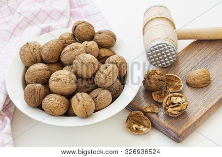 Natural Unbleached Walnuts (juglans Regia) In A White Bowl. Cracked Nuts And Wooden Meat Mallet On A