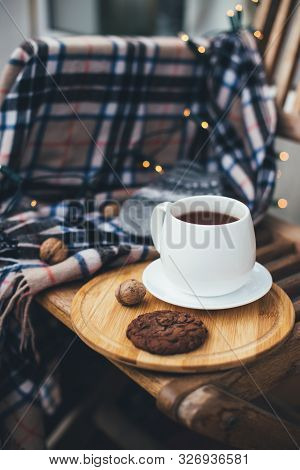 Still Life With Hot Tea And Chocolate Cookies On Wooden Tray With Warm Blanket And Festive Lights On