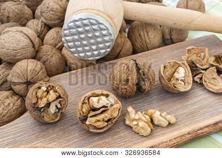 Cracked Walnuts (juglans Regia) And Kernels On A Brown Wooden Board Near Wooden Meat Mallet. Natural
