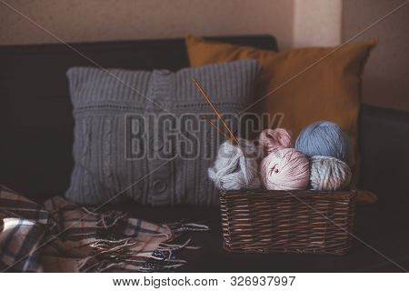 Balls Of Woolen Yarn And Knitting Needles In Basket In Cozy Interior.
