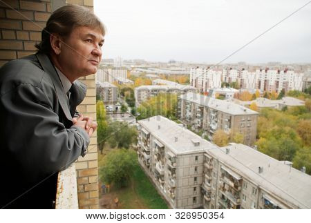 Man In A Gray Cloak Thoughtfully Looks At The City From The Balcony Of A Multi-storey Building. Dayd