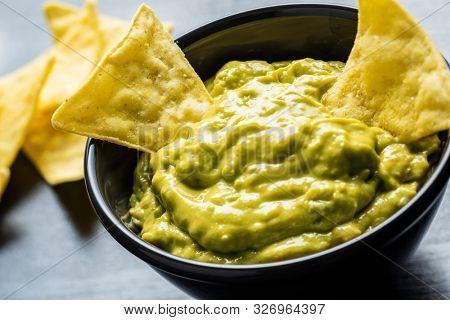 Corn nacho chips and avocado dip. Yellow tortilla chips and guacamole in bowl.