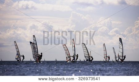 Silhouettes Of A Group Of Windsurfers In Open Water On The Horizon. Blurred Foreground.