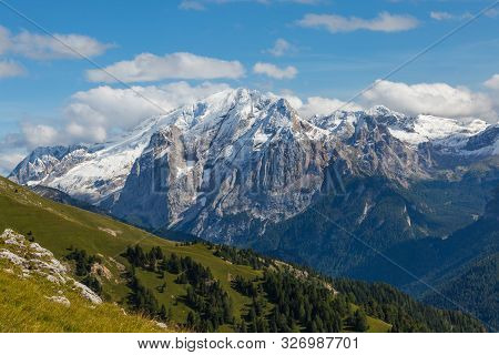 Marmolada Dolomite Mountains In Summer, Green Meadow, Blue Sky
