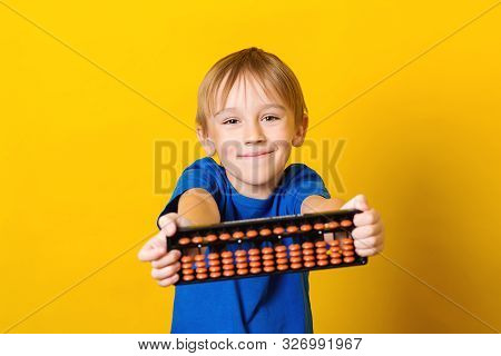 Happy Boy Holding Abacus Over Yellow Background. Mental Arithmetic School. Kids Development, Skill A