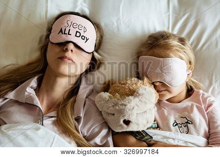 High View Of Caucasian Mother And Daughter, Stuffed Teddy Bear Toy Sleeping In Blindfolds On The Bed