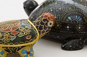 close up of two turtle trinkets in cute pose against white background. high kitsch value. poster