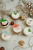 New Years sweets on a marble table. Christmas cupcakes decorated with mastic and cream. poster
