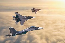 Group Of Three Aircraft Fighter Jet Airplane Sun Glow Flying High In The Sky Above The Clouds