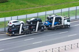 Highway Transportation Of New Cars On A Trailer With A Truck For Delivery To Dealers