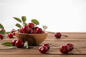 Ripe Cherries In A Wooden Bowl On The Background Of Wooden Boards