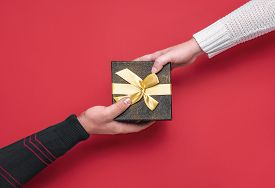 Giving And Receiving Festive Gift Box. Christmas Gifting Time Concept. Man And Woman Hands On A Blac