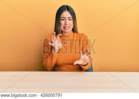 Young hispanic woman wearing casual clothes sitting on the table disgusted expression, displeased and fearful doing disgust face because aversion reaction.