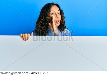 Middle age hispanic woman holding blank empty banner hand on mouth telling secret rumor, whispering malicious talk conversation