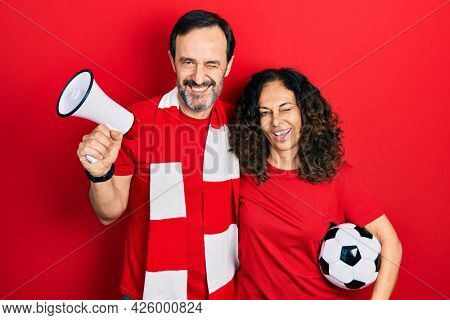 Middle age couple of hispanic woman and man wearing team scarf cheering game holding megaphone and ball winking looking at the camera with sexy expression, cheerful and happy face.