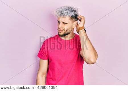 Young hispanic man with modern dyed hair wearing casual pink t shirt confuse and wondering about question. uncertain with doubt, thinking with hand on head. pensive concept.