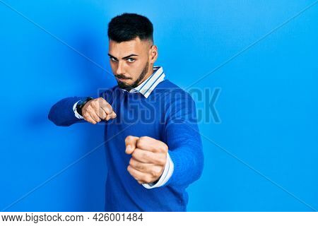 Young hispanic man with beard wearing casual blue sweater punching fist to fight, aggressive and angry attack, threat and violence