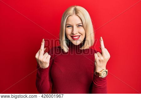 Young blonde woman wearing casual clothes showing middle finger doing bad expression, provocation and rude attitude. screaming excited