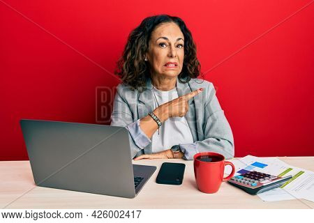 Beautiful middle age woman working at the office drinking a cup of coffee pointing aside worried and nervous with forefinger, concerned and surprised expression