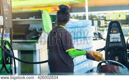 Woman Staff Hold Yellow Fuel Nozzle To Refilling The Motorcycle In The Gas  Station,