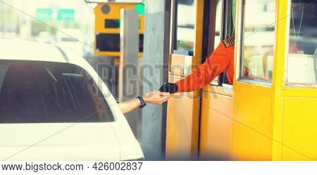 Selective Focus To Hand Of Driver Pay For The Expressway. Driver Pays Money To A Cashier For A Toll