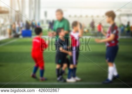 Blurry Kid Soccer Players Standing With Coach On Green Artificial Turf.