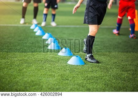 Selective Focus To Cone Marker With Blurry Kid Soccer Is Running On Green Artificial Turf.