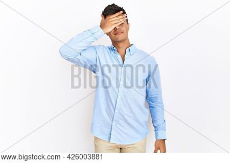 Young hispanic man wearing business shirt standing over isolated background covering eyes with hand, looking serious and sad. sightless, hiding and rejection concept