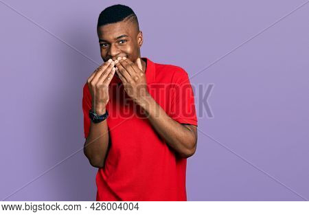 Young african american man wearing casual red t shirt laughing and embarrassed giggle covering mouth with hands, gossip and scandal concept