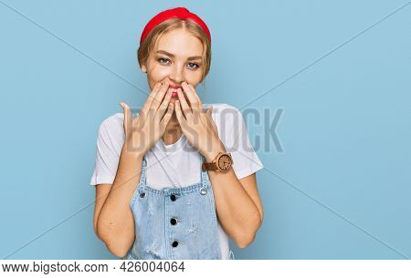 Young caucasian girl wearing casual clothes laughing and embarrassed giggle covering mouth with hands, gossip and scandal concept