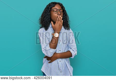 Beautiful african young woman wearing casual clothes and glasses bored yawning tired covering mouth with hand. restless and sleepiness.