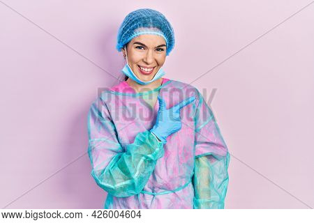 Young brunette woman wearing surgeon uniform and medical mask cheerful with a smile of face pointing with hand and finger up to the side with happy and natural expression on face