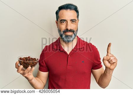 Middle age man with beard and grey hair holding raisins bowl smiling with an idea or question pointing finger with happy face, number one
