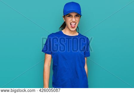 Young hispanic girl wearing delivery courier uniform sticking tongue out happy with funny expression. emotion concept.