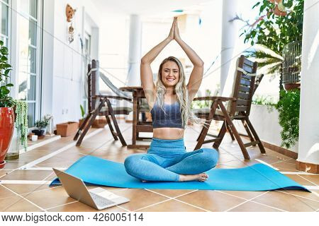 Beautiful caucasian woman doing exercise and stretching at the terrace at her home. Doing asana and wellbeing work out on yoga mat looking at traning tutorial on laptop.