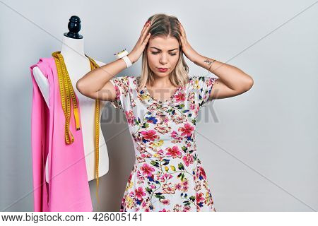 Beautiful caucasian woman dressmaker designer by manikin suffering from headache desperate and stressed because pain and migraine. hands on head.
